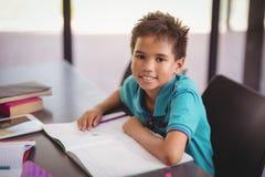 Ritratto dello scolaro sorridente che fa il suo compito in biblioteca Fotografia Stock