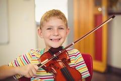 Ritratto dello scolaro sorridente che gioca violino in aula Immagini Stock Libere da Diritti