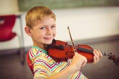 Ritratto dello scolaro sorridente che gioca violino in aula Immagini Stock
