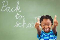 Ritratto dello scolaro sorridente che mostra i pollici su nell'aula Immagini Stock