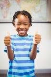 Ritratto dello scolaro sorridente che mostra i pollici su nell'aula Fotografie Stock Libere da Diritti