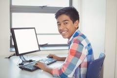 Ritratto dello scolaro sorridente che per mezzo del computer Fotografia Stock