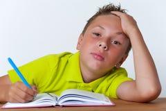 Ritratto dello scolaro stanco che si siede con il libro Fotografia Stock Libera da Diritti