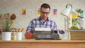 Ritratto dello scrittore del giovane che scrive con l'ispirazione su una vecchia macchina da scrivere archivi video