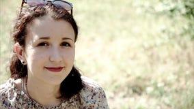 Ritratto dello sguardo sorridente della ragazza in camera e sedendosi sull'erba video d archivio