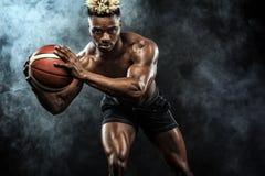 Ritratto dello sportivo afroamericano, giocatore di pallacanestro con una palla sopra fondo nero Giovane adatto in abiti sportivi Fotografia Stock