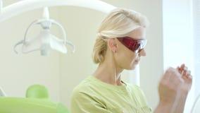 Ritratto dello stomatologo che tiene luce di trattamento dentaria per la cavità orale video d archivio