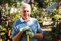Ritratto dello strumento di tenuta felice del giardiniere al giardino Fotografia Stock Libera da Diritti