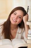 Ritratto dello studente abile con il libro aperto che lo legge nella biblioteca di istituto universitario che tiene una penna Immagini Stock Libere da Diritti