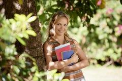 Ritratto dello studente al banco, giovane donna felice con l'università BO Immagini Stock
