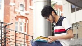 Ritratto dello studente asiatico dell'uomo che si siede sulle scale e sul libro di lettura stock footage