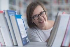 Ritratto dello studente del famale che seleziona libro leggere dentro biblioteca Fotografie Stock Libere da Diritti