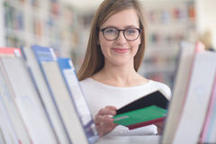 Ritratto dello studente del famale che seleziona libro leggere dentro biblioteca Fotografia Stock Libera da Diritti