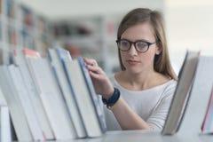 Ritratto dello studente del famale che seleziona libro leggere dentro biblioteca Fotografia Stock