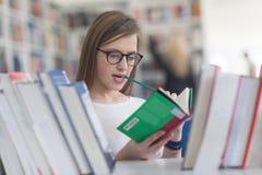 Ritratto dello studente del famale che seleziona libro leggere dentro biblioteca Fotografie Stock