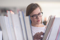 Ritratto dello studente del famale che seleziona libro leggere dentro biblioteca Immagine Stock
