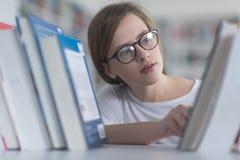 Ritratto dello studente del famale che seleziona libro leggere dentro biblioteca Immagini Stock
