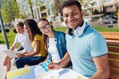 Ritratto dello studente internazionale sorridente quella posa sulla macchina fotografica Immagine Stock