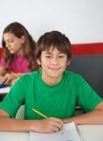 Ritratto dello studente maschio adolescente Sitting At Desk Immagini Stock