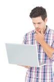 Ritratto dello studente maschio premuroso che per mezzo di un computer portatile Fotografie Stock Libere da Diritti