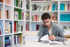 Ritratto dello studente mentre libro di lettura nella biblioteca di scuola Immagini Stock