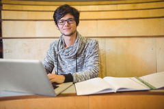 Ritratto dello studente sorridente che utilizza computer portatile nell'aula Immagini Stock Libere da Diritti