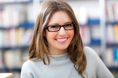 Ritratto dello studente in una biblioteca Fotografia Stock