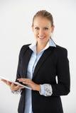 Ritratto dello studio del fondo di Standing Against White della donna di affari facendo uso della compressa di Digital Fotografia Stock