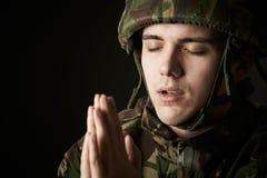 Ritratto dello studio del soldato In Uniform Praying fotografia stock
