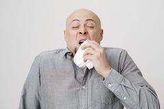 Ritratto dello studio del tovagliolo o del tessuto caucasico calvo malato della tenuta dell'uomo, provante a coprire bocca mentre Fotografie Stock Libere da Diritti
