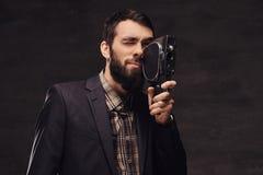Ritratto dello studio dell'uomo barbuto che indossa un vestito classico che tiene una retro macchina fotografica, facente una fot fotografie stock