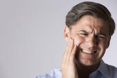Ritratto dello studio dell'uomo che soffre con il mal di denti Fotografia Stock