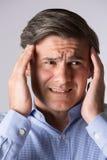 Ritratto dello studio dell'uomo che soffre con l'emicrania fotografia stock