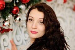 Ritratto dello studio della giovane donna sveglia con capelli scuri ricci sul fondo della decorazione di Natale con rosso ed il v Fotografia Stock