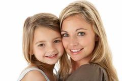 Ritratto dello studio della madre che abbraccia giovane figlia fotografia stock