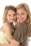 Ritratto dello studio della madre che abbraccia giovane figlia Immagini Stock