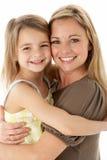 Ritratto dello studio della madre che abbraccia giovane figlia immagini stock libere da diritti