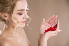 Ritratto dello studio di una bionda nelle sue capsule rosse delle mani della vitamina Immagine Stock