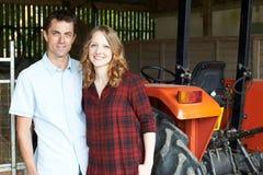 Ritratto di agricoltura delle coppie che stanno nel granaio con il trattore Immagine Stock