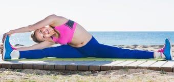 Ritratto di allungamento d'esercitazione femminile sorridente Fotografie Stock
