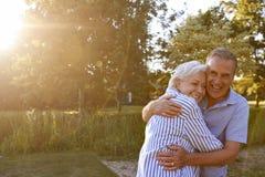 Ritratto di amore delle coppie senior che abbracciano aria aperta nel parco di estate contro il Sun scintillante fotografia stock