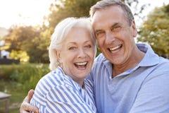 Ritratto di amore delle coppie senior che abbracciano aria aperta nel parco di estate contro il Sun scintillante fotografie stock