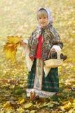 Ritratto di autunno della bambina nel sarafan e nel foulard russi tradizionali che riunisce le foglie e i pinecones di giallo Immagini Stock Libere da Diritti