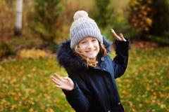 ritratto di autunno della ragazza felice del bambino che cammina nel giardino in cappotto caldo del parka fotografie stock