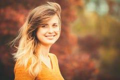 Ritratto di autunno di un fronte femminile contro un fondo di fogliame arancio nel parco Fotografia Stock