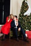 Ritratto di bella coppia su un fondo dell'albero di Natale Nuovo anno, vestito rosso, vestito blu fotografia stock
