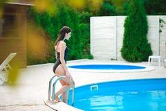 Ritratto di bella donna abbronzata in swimwear nero che si rilassa nella stazione termale della piscina immagine stock
