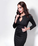Ritratto di bella donna adulta di sensualità in vestito nero che posa sopra il fondo bianco Vista sul lato Fotografie Stock Libere da Diritti