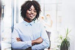 Ritratto di bella donna africana felice che sta con le armi piegate ed i colleghi su fondo in sottotetto moderno Immagini Stock Libere da Diritti
