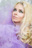 Ritratto di bella donna bionda con capelli lunghi e ricci che si siedono dietro la finestra di vetro, avvolti a Tulle porpora Immagine Stock
